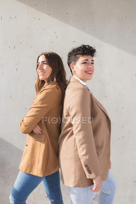 Vista lateral de jovens mulheres sorridentes em roupas elegantes que ficam de costas para trás enquanto olham para longe em dia ensolarado perto da parede cinza — Fotografia de Stock