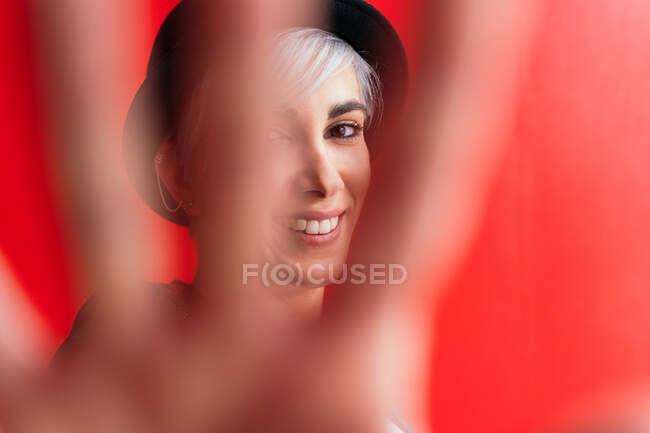 Молода жінка в капелюсі демонструє жест управління, дивлячись на камеру з зубатою посмішкою. — стокове фото