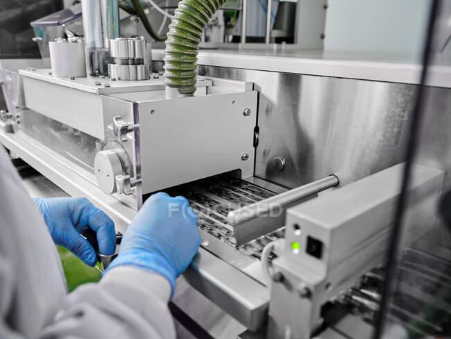 Cultivo irreconocible trabajador de fábrica en guantes que trabajan en el transportador automático con cápsulas en blisters en la planta de fabricación farmacéutica - foto de stock