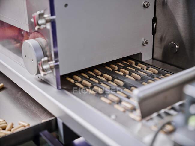 Pastillas en blisters sobre transportador metálico en laboratorio farmacéutico - foto de stock