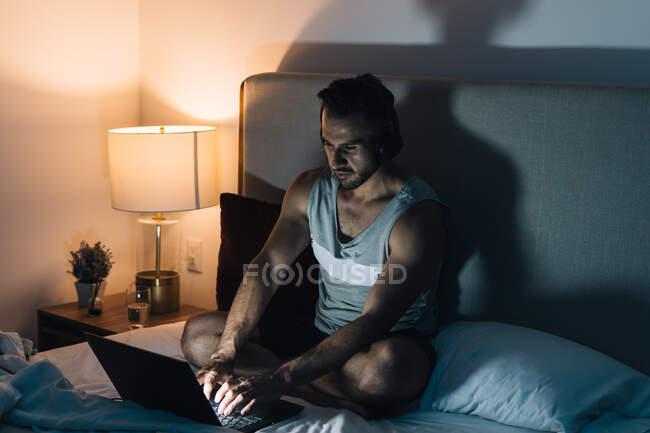Freelance masculin concentré dans les écouteurs assis sur le lit et le netbook de navigation tout en travaillant sur un projet à distance à la maison le soir — Photo de stock