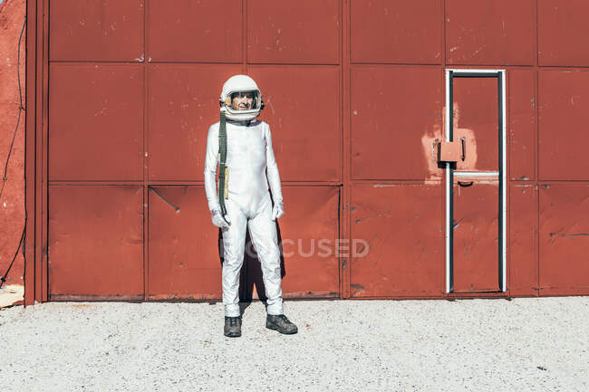 Man in spacesuit standing near red wall of industrial facility on sunny day — Stock Photo