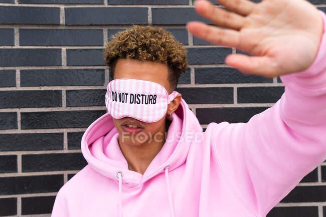 Неупізнаваний молодий кучерявий етнічний хлопець в рожевій копиці і в зав'язці з текстом Do Not Disturb робить стоп жест до цегляної стіни — стокове фото
