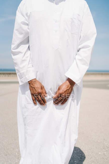 Cultiver mâle islamique en vêtements blancs traditionnels debout sur le tapis et prier contre le ciel bleu sur la plage — Photo de stock