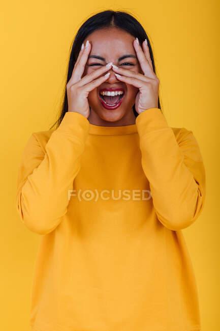 Délicieuse asiatique femelle crier et toucher le visage sur fond jaune en studio tout en regardant la caméra — Photo de stock