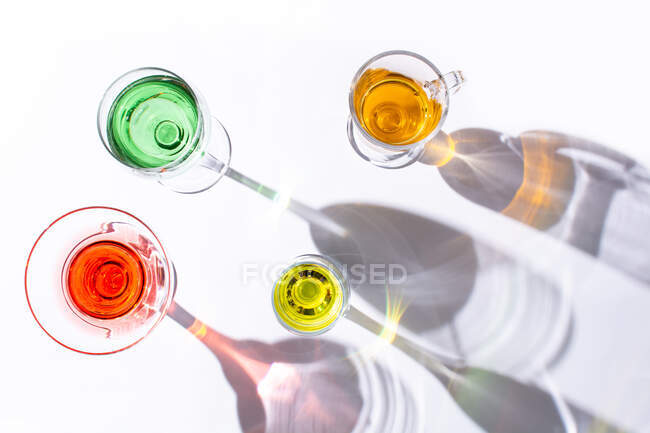 Top view of different types of glasses with colorful liquid inside on white background — Stock Photo