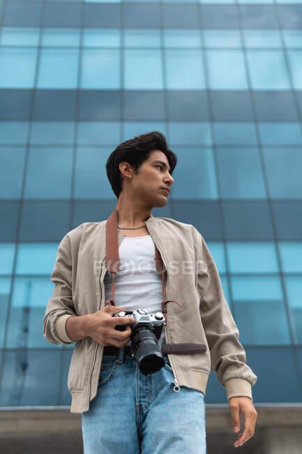 D'en bas jeune homme latin photographe tenant appareil photo regardant loin contre le bâtiment moderne — Photo de stock