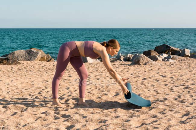 Vue latérale complète du corps de la jeune femme en vêtements de sport plaçant tapis de yoga sur le sable tout en se préparant pour la pratique sur la plage près de l'océan — Photo de stock