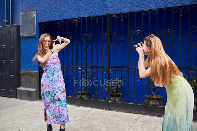 Femme avec appareil photo prenant une photo de petite amie en robe d'été debout dans la rue et montrant le geste de cadrage — Photo de stock