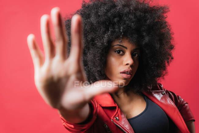Перелякана афро-американська жінка з кучерявим волоссям показує стоп жест на червоному фоні в студії і дивиться на камеру — стокове фото