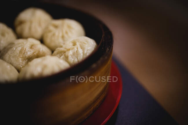 Hot delicious steamed xiaolongbao in bamboo basket on table in Asian restaurant kitchen — Stock Photo