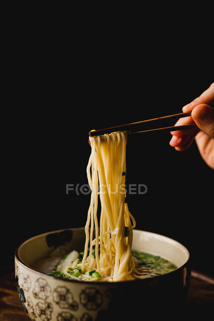 Hand of woman holding bamboo chopsticks with tasty wheat noodles from Chinese ramen meal plate — Stock Photo