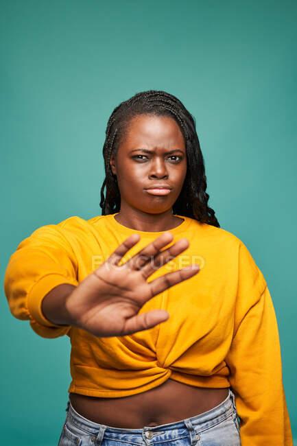 Афроамериканська жінка в жовтому одязі демонструє захисний жест з витягнутою рукою на синьому фоні — стокове фото