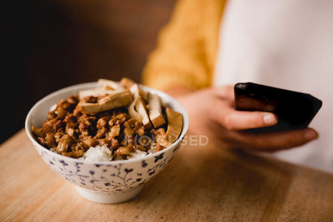 Bowl with traditional Taiwanese Lu Rou Fan dish placed on wooden table near female with smartphone in cafe — Stock Photo