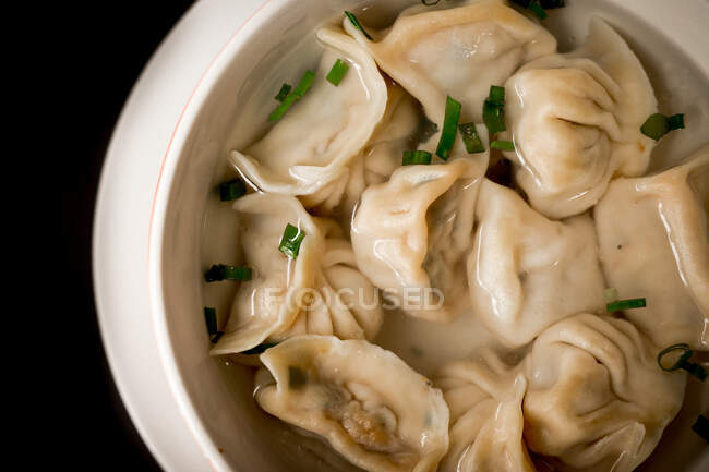 Closeup bowl of delicious soup with dumplings and spring onion against black background — Stock Photo