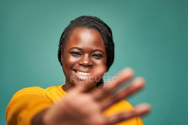 Радісна афро-американська жінка в жовтому одязі демонструє захисний жест з витягнутою рукою на синьому тлі — стокове фото
