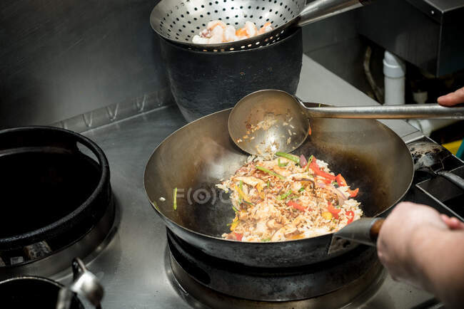 High angle of crop anonymous chef frying rice with vegetables in wok while cooking dish with prawns in kitchen of restaurant — Stock Photo