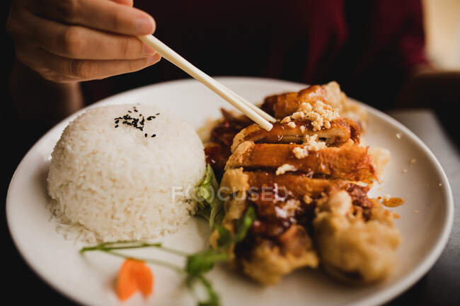Woman sitting in Asian cafe and eating hot appetizing spicy duck with rice — Stock Photo