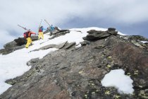 Cross-country skiers climbing on rocks — Stock Photo