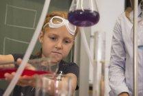 Schoolgirl mixing liquid in chemistry class — Stock Photo