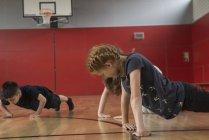 Crianças fazendo flexões no pavilhão desportivo — Fotografia de Stock