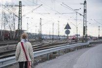 Mujer mirando curiosamente el tren - foto de stock