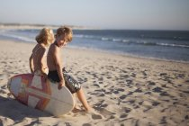 Children sitting on bodyboard at the beach — Stock Photo