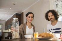 Casal com café da manhã na mesa de jantar — Fotografia de Stock