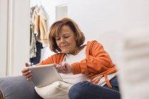 Расслабленная пожилая женщина работает с планшетом — стоковое фото