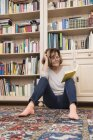 Woman sitting on floor at bookshelf and reading — Stock Photo