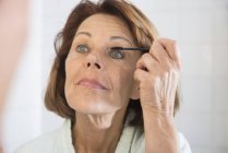 Senior woman applying mascara — Stock Photo