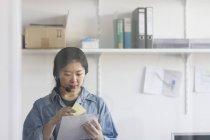 Assistente tecnico femminile indossa auricolare e lavorando — Foto stock