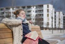 Giovane donna seduta sulla panchina in città — Foto stock