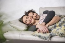 Mid adult couple sleeping on sofa — Stock Photo