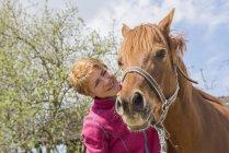 Женщина проявляет привязанность к своей лошади — стоковое фото