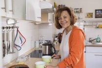 Haute femme prépare le thé dans la cuisine — Photo de stock