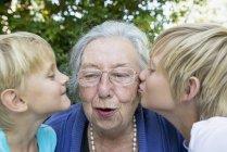 Внуки целуют ее бабушку — стоковое фото