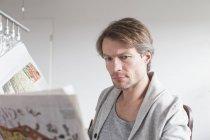 Maturo Uomo leggendo giornale — Foto stock