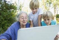 Abuela y nietos con portátil - foto de stock