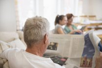 Grandfather reading newspaper in living room — Stock Photo