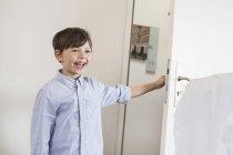 Garçon ouverture porte à la maison — Photo de stock