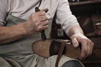 Shoemaker working in workshop — Stock Photo