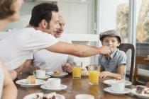 Candid famille prenant son petit déjeuner à table — Photo de stock