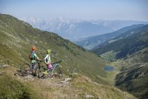 Bikers looking at view in alpine landscape — Stock Photo