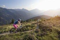 Mountainbiker fahren auf Hügel in alpiner Landschaft — Stockfoto