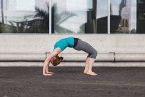 Женщина делает мост поза на улице — стоковое фото