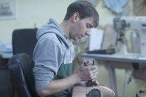Shoemaker repairing shoe — Stock Photo