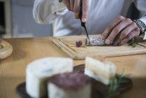Salame di taglio uomo in cucina — Foto stock