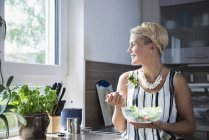 Woman eating salad in kitchen — Stock Photo