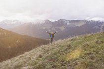 Woman with arms raised standing in mountain — Stock Photo